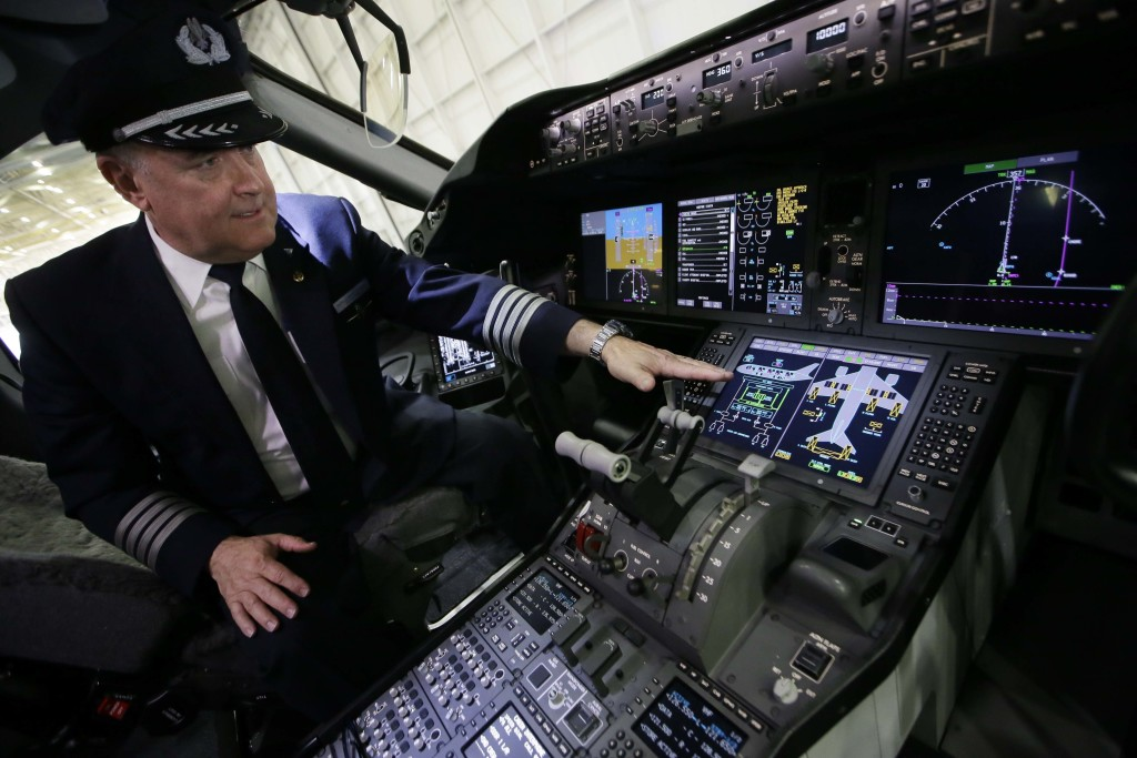 Captain Bruce Johnson explains the cockpit instruments of American Airlines' first Boeing 787 Dreamliner at the airline's maintenance hangar at Dallas-Fort Worth International Airport, Wednesday, April 29, 2015, in Grapevine, Texas. American Airlines unveiled the new passenger jet to employees and media before it goes into service May 7. (AP Photo/LM Otero)